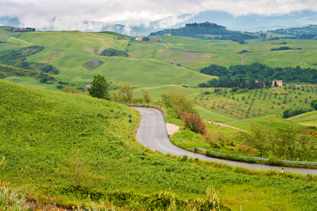 Winding road in green hills Tuscany, Italy photo