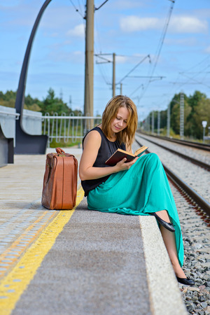 long skirt: Young attractive girl in long skirt sitting on the train station and reading a book Stock Photo