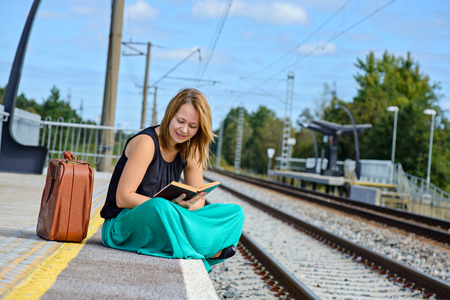 Young attractive woman in long skirt sitting on the train station and reading a book photo