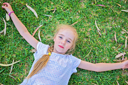extend: Caucasian small girl extend your arms lying on green grass, top view Stock Photo