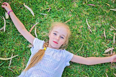 porgere: Caucasica piccola ragazza estendere le braccia disteso sul prato verde, vista dall'alto Archivio Fotografico