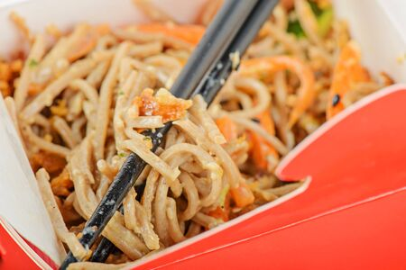take out food: Closeup of meat and noodles in red take away container. Shallow depth of field. Stock Photo