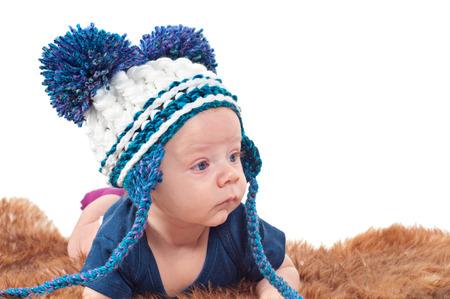 pompom: Ritratto del primo piano del bambino adorabile in cappello con pon-pon si trova sulla pelliccia