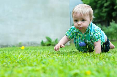 bebe gateando: Bebé lindo que se arrastra en la hierba cerca de la casa Foto de archivo