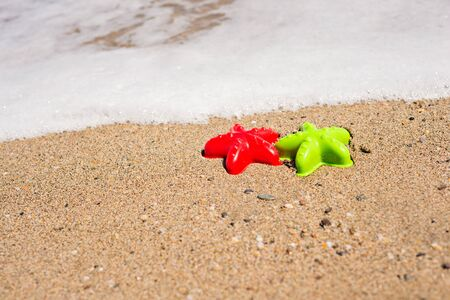 sand mold: Red and green starfish-shaped molds on the sand with wave Stock Photo