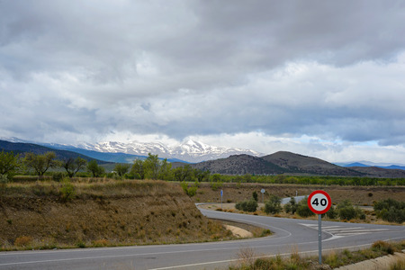 km: Zigzag road in Spain with snow mountains on background and speed limit 40 km h Stock Photo
