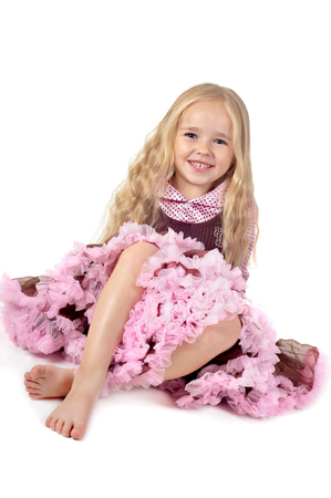 Happy little girl in tutu skirt sitting on the floor isolated on a white background