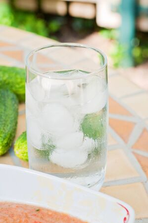 Shot of glass water with ice on the table. Part of plate with gazpacho and cucumbers. Stock Photo