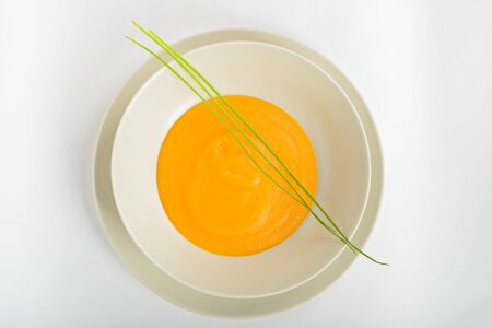 Delicious healthy pumpkin soup in a light dish. View from above. Stock Photo