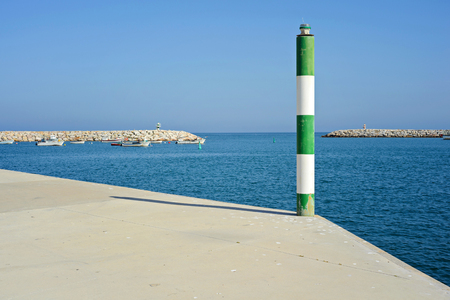 white pole: Green and white pole on the pier, blue sea and sky Stock Photo