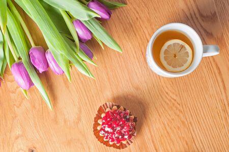 arreglo floral: Vista superior a la tulipanes violetas frescas, pasteles y té en la mesa de madera