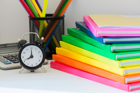 Concept of education. Black alarm clock. Multi colored books in stack on the light-coloured bookshelf, calculator and pencils in case on the background Stock Photo