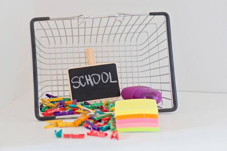 Back to School shopping with shopping basket. Items on the on the light-coloured shelf. Concept of education.