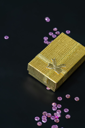 sequins: Gold christmas gift box and pink sequins on dark background