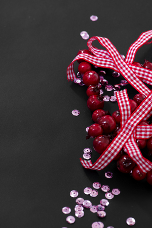 sequins: Christmas decoration and pink sequins on dark background, vertical