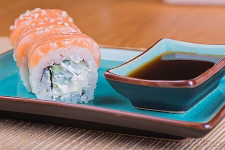 azul: California maki sushi with salmon. Roll made of salmon, cream cheese and  cucumber on azul plate. Shallow depth of field.
