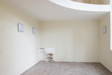 wooden floors: New home construction interior living room with unfinished tile wooden floors and balcony. The heating system also are partially unfinished.