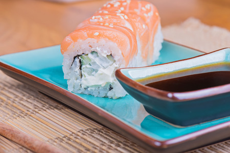 azul: California maki sushi with salmon and soy sauce. Roll made of salmon, cream cheese and  cucumber on azul plate. Shallow depth of field.