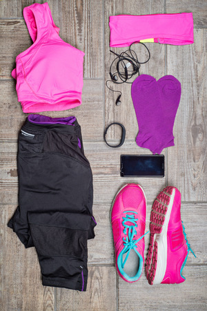 Overhead view of athlete's set with female clothing and equipment on wooden background