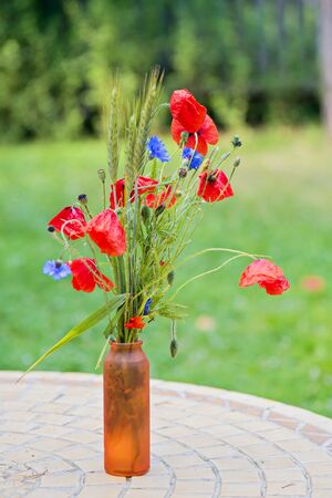 barley head: Bunch of of red poppies, cornflowers and ears of barley, wheat and rye on the table. Shallow depth of field. Blurred background