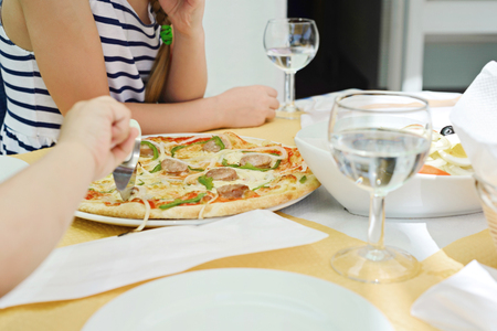 somebody: Somebody cutting pizza using pizza knife. Glasses with water on the table. Stock Photo