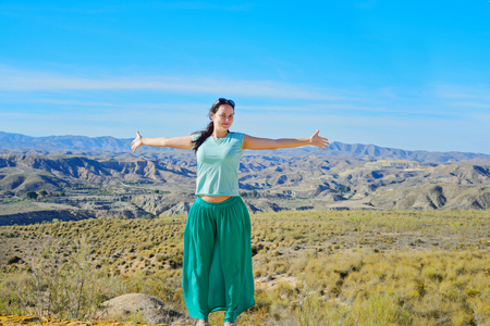 Young happy woman open arms stand at mountain in spanish desert