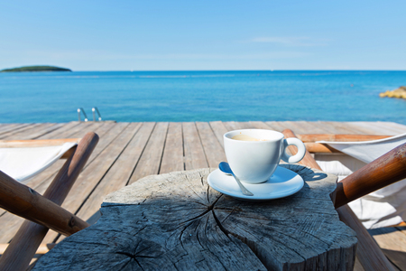 Wooden floor and sea view with chaise-longues and cup of coffee, Istria, Croatian coast Stock Photo