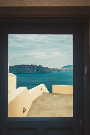 Window with view of Thira and caldera of Santorini volcano, Greece. Dramatic toning Stock Photo