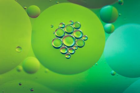 Oil drops in water. Abstract defocused psychedelic pattern image green colored. Abstract background with colorful gradient colors.