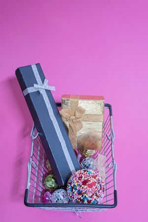 Many christmas toys and gifts in shopping basket over pink background