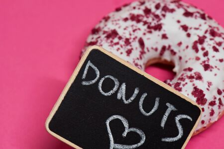 Macro shoot of white donut over pink background
