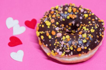 Macro shoot of chocolate donut over pink background