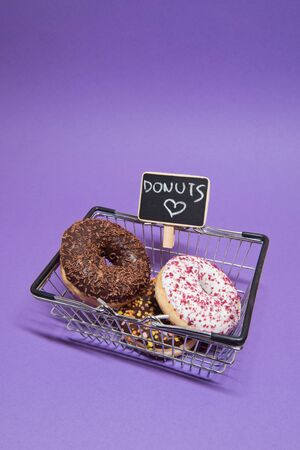 Macro shoot of donuts in shopping basket over purple background