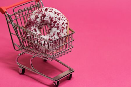 Macro shoot of white donut in shopping trolley over pink background