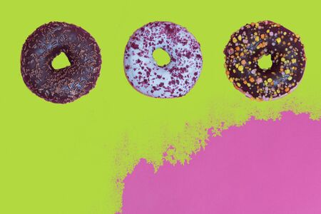 Top view to the donuts over green and pink background