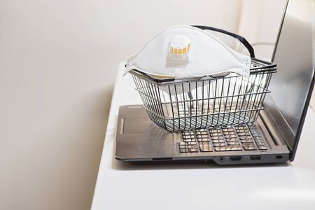 Conceptual photo with miniature shopping-basket and protecting mask and glasses. Safety internet shopping Banque d'images