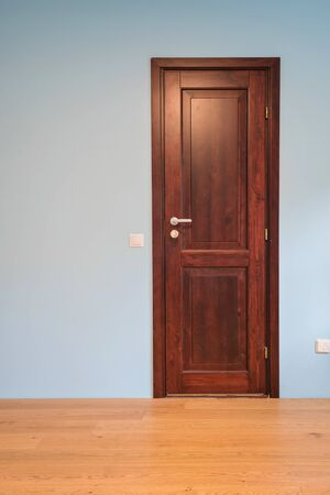 Frontal view to the wooden door in home interior room with wooden floors and blue walls.