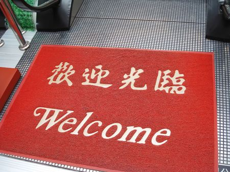 Mat at the entrance. With a greeting Welcome on english and chinese photo