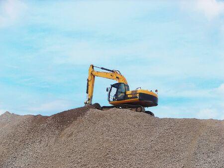 Excavadora amarillo, trabajando en una montaña de escombros       Foto de archivo