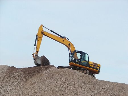 Yellow Excavator working on a mountain of rubble photo