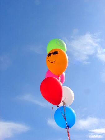 Many colored balloons in the blue sky photo