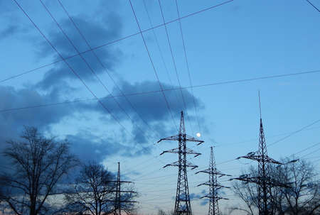 over voltage: Full moon over pylons of high voltage power line Stock Photo