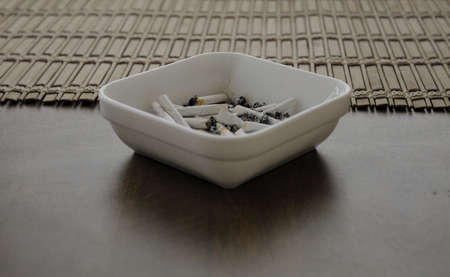 ashtray: Woman ashtray with thin cigarette butts Stock Photo