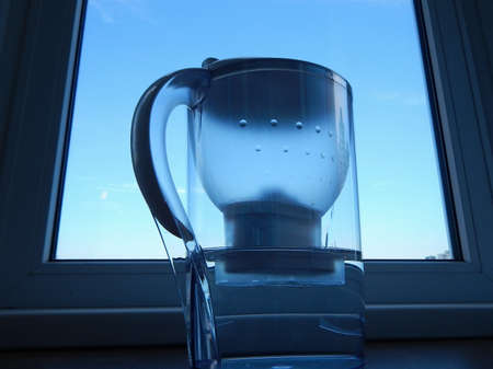 purified: Home water filter with purified water at windowsill