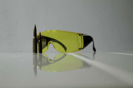 hunter's: Hunters equipment. Special yellow shooting glasses and rifle bullets isolated Stock Photo