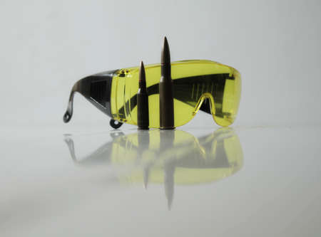 shooters: Hunters equipment. Special yellow shooting glasses and rifle bullets isolated Stock Photo