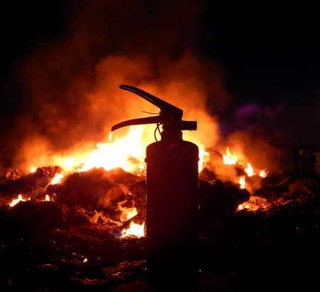 explosive hazard: Fire extinguisher over burning fire at night closeup Stock Photo