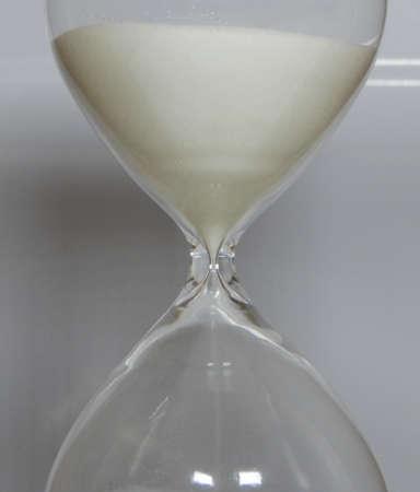 count down: Sandglass over white background studio shot Stock Photo