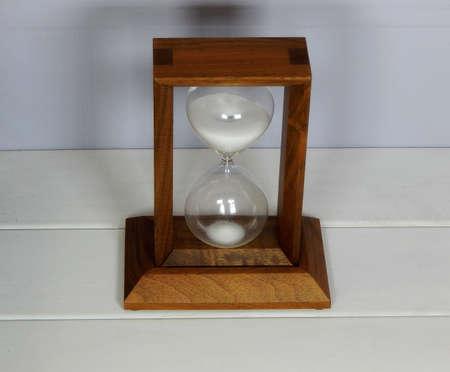 reversing: Sandglass over white background studio shot Stock Photo