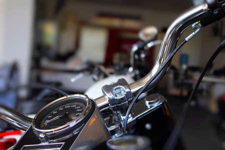Snelheidsmeter en verchroomde delen op motorfiets stuur in motor winkel Stockfoto